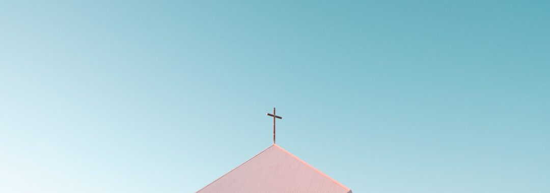 Church steeple with blue sky backdrop.